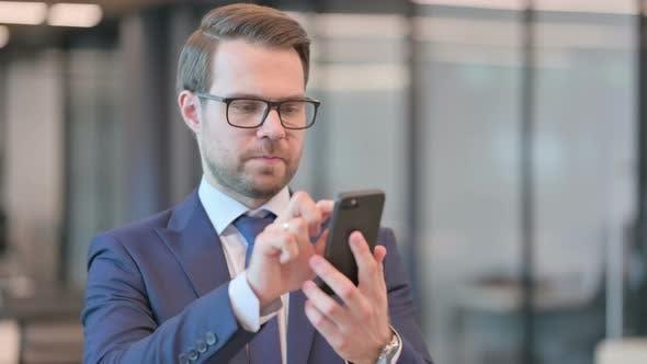 Portrait of Businessman Browsing Internet on Smartphone