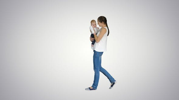 Young mother holding her baby in hands and walking, Alpha Channel