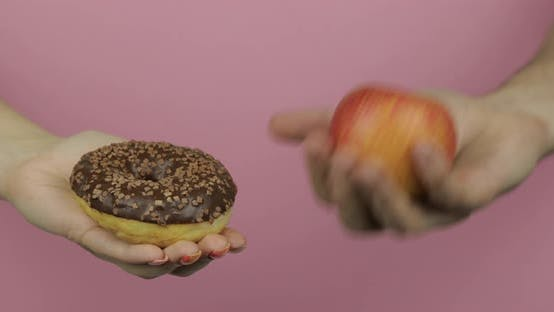 Thumbnail for Hands Holds Donut and Apple. Choice Donut Against Apple. Healthy or Junk Food