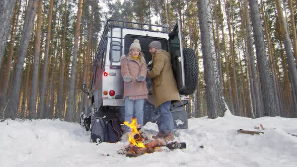 Cover Image for Couple Warming at Campfire