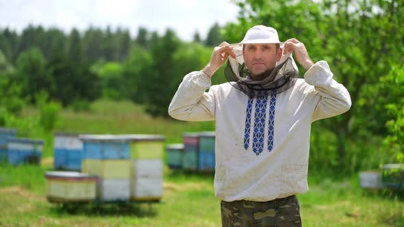 Portrait of beekeeper on apiary