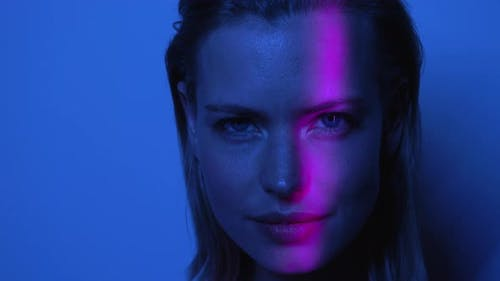 Pink Light Moves Around Beautiful Models Face in Dark Room