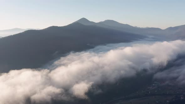 Thumbnail for Fog above mountain valley at sunrise. Aerial view of morning mountain landscape.