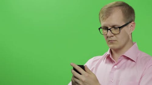 Caucasian Man Scrolling, Texting on the Smartphone. Place for Your Logo or Text