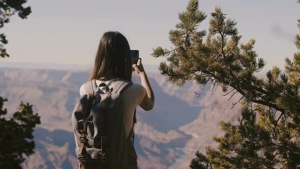 Cover Image for Back View Happy Tourist Woman Hiking, Taking Smartphone Photo of Amazing Grand Canyon National Park