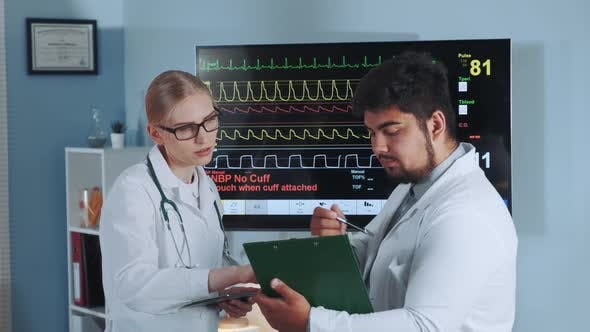 Thumbnail for Female Doctor and Her Mixed Race Colleague Discussing EKG Data of the Athlete