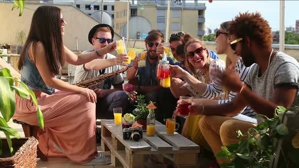 Group of happy multi-ethnic friends toasting with cocktails at rooftop party
