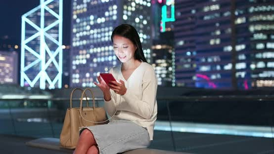Thumbnail for Woman send sms on cellphone in city at night