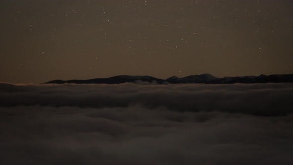 Time Lapse of Fog and Stars During the Night with Mountains in the Background