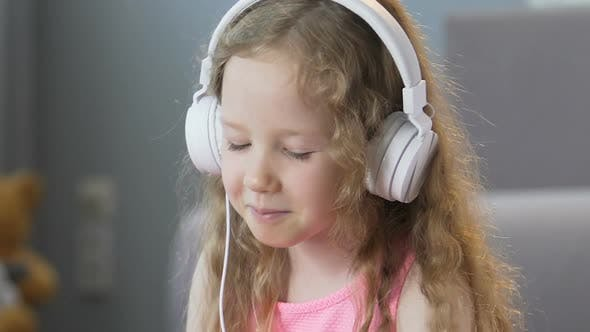Thumbnail for Nice Curly-Haired Girl Listening to Music in Headphones