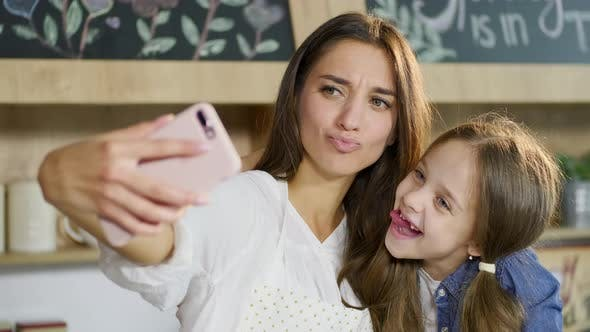 Thumbnail for Beautiful Picture of Funny Happy Mother and Daughter Without Dairy Tooth Grimacing on the Phone