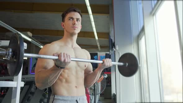 Thumbnail for Ripped Shirtless Young Bodybuilder Lifting Barbell, Doing Biceps Exercise