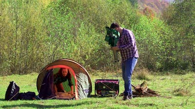 Boyfriend Sitting on Camping Seat While Girlfriend Preparing the Tent
