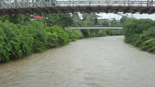 Moving over a large river with a brown coloration under a old bridge