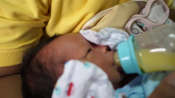 The newborn is eating breast milk from a bottle, slow-motion shot