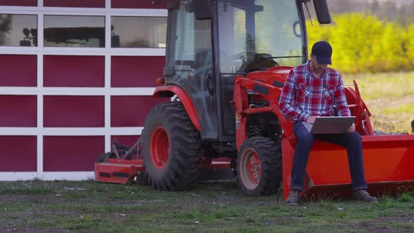 Farmer sits on tractor using laptop computer