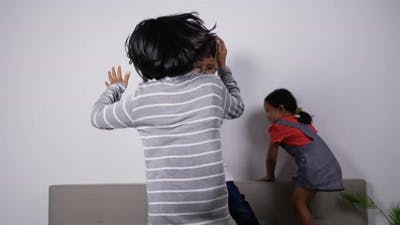 Funny asian kids dancing on sofa in living room at home.
