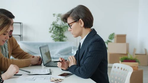 Young Family Discussing Sales Contract with Real Estate Specialist Reading Document Indoors