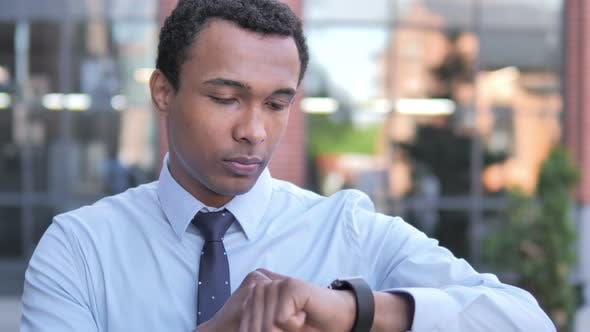 Thumbnail for African Businessman Using Smartwatch Outdoor