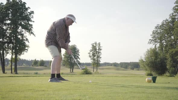 Thumbnail for Portrait Successful Mature Golfer Swinging and Hitting Golf Ball on Beautiful Course. Confident Man