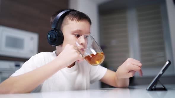Junge trinkt Tee auf dem Tisch. Junge trinkt Tee am Küchentisch und benutzt digitales Tablet