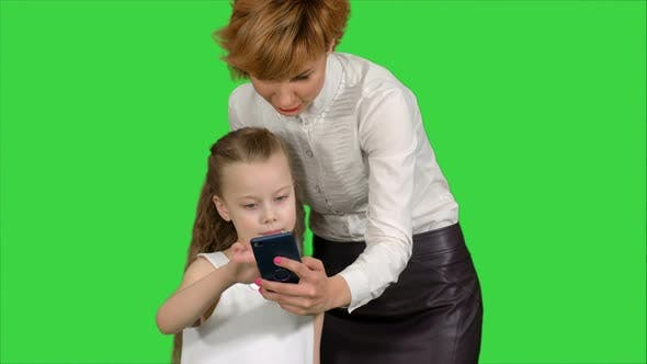Young Mother Teaching Her Daughter How To Use Smartphone on a Green Screen, Chroma Key