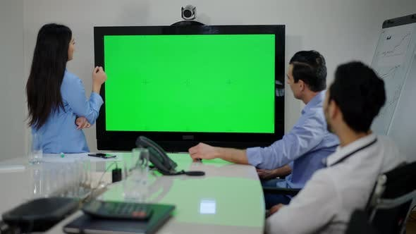 Big Chromakey Monitor in Modern Office with Thoughtful Multiethnic Coworkers Brainstorming