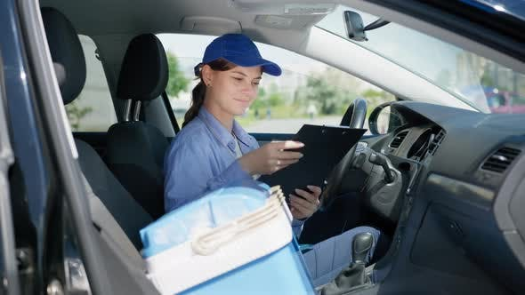 Thumbnail for Young Attractive Woman Driver Working As Courier in Food Supply Service of Shop at Home Checks