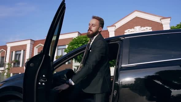 Thumbnail for Young Caucasian Businessman in Formal Suit with Tie Gets Out of the Black Car