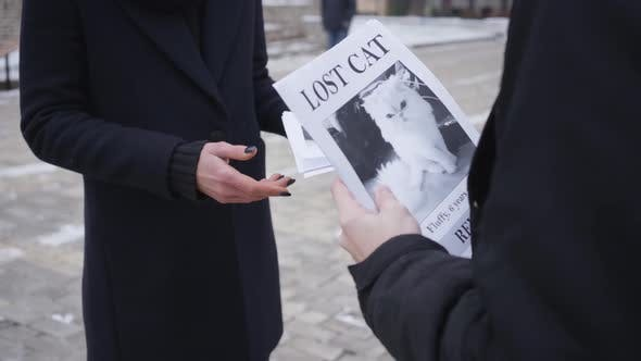 Unrecognizable Caucasian Man Giving Missing Cat Ad To Young Woman on the Street, People Going Out