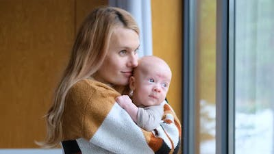 woman hugs and kisses toddler boy standing by the window