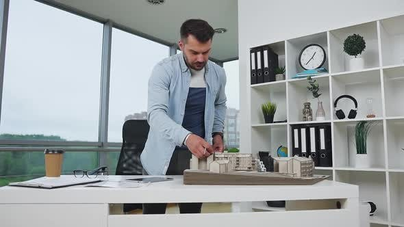 Thumbnail for Bearded Engineer-Designer Using Ruler Taking Measurements of Constructed Building's Model