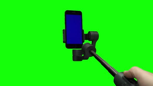 Thumbnail for Filmmaker's Hand Lifting Up Steadicam with Blue Screen on Smartphone