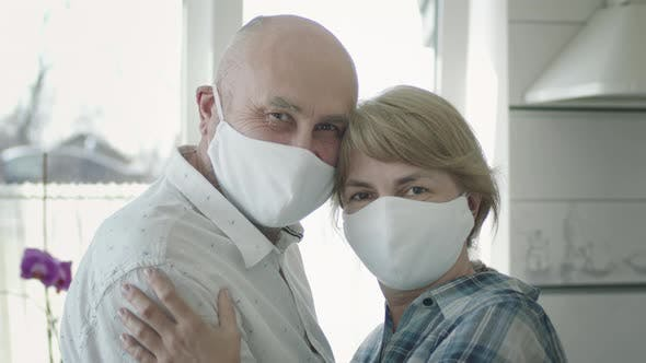 Portrait Of Mature Couple In Medical Masks In Guarantine. They Cuddle.