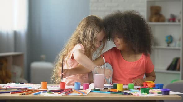 Thumbnail for At Kindergarten, Two Positive Multiracial Girls Painting with Watercolors, Hobby