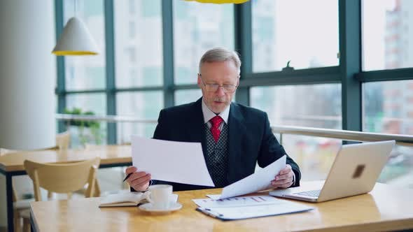 Thumbnail for Businessman is reading a printed report or document while sitting at the table