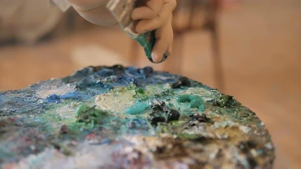 Thumbnail for Künstler setzt grüne Farbe auf Palette aus Tube im Studio