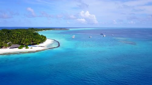 Tropical drone travel shot of a white sand paradise beach and turquoise sea background in vibrant 4K