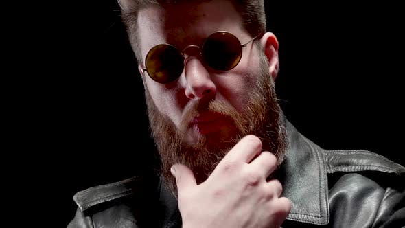 Thumbnail for Serious Man with Heavy Metal Look Chews Tabacco and Touches His Beard