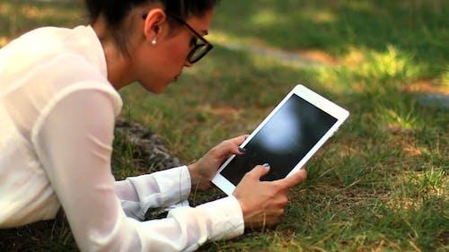 mädchen mit tablet im park 01