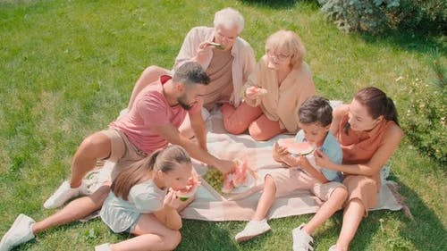 Multigenerational Family Eating Watermelon On Lawn