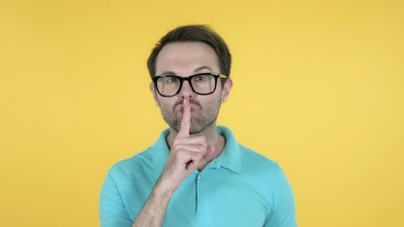 Thumbnail for Man Gesturing Silence, Finger on Lips, Yellow Background
