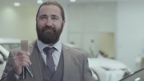 Thumbnail for Portrait of a Successful Bearded Business Man in a Business Suit Showing the Key of a Luxury Car