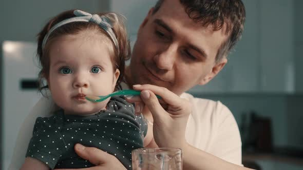 Thumbnail for Young Parents Feed Baby Daughter at Home
