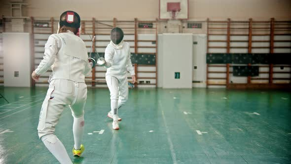 Thumbnail for Two Young Women in Protective Costumes and Helmets at the Fencing Training in the School Gym