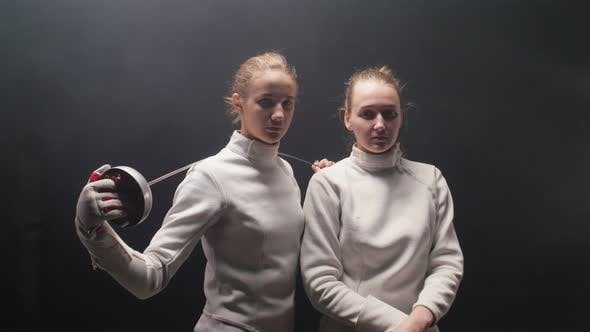 Cover Image for Two Young Women Fencers Standing in the Dark Studio - Posing for the Camera