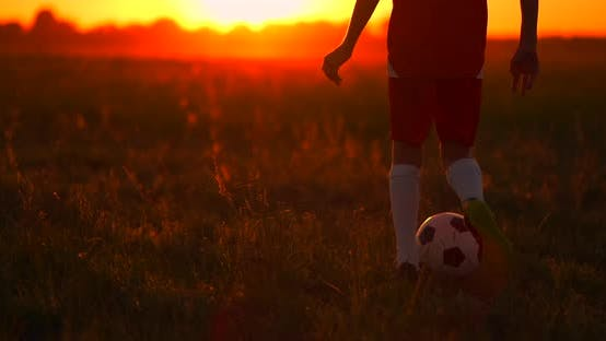 Thumbnail for Tracking a Boy Football Player Running with a Ball at Sunset in the Field