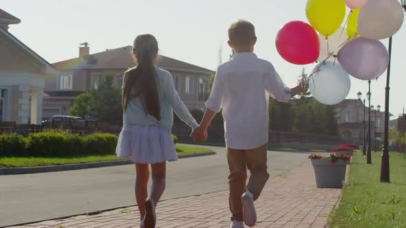 Thumbnail for Little Boy and Girl Holding Hands and Walking with Balloons