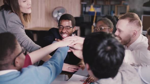 Thumbnail for Happy Successful Multiethnic Business People Joining Hands, Encouraged By Caucasian Female Team