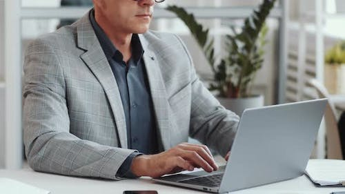 Midsection of Businessman Working on Laptop at Office Desk